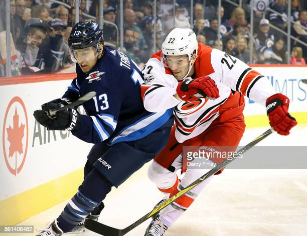 Brandon Tanev of the Winnipeg Jets and Brett Pesce of the Carolina Hurricanes battle as they chase the play along the boards during first period...