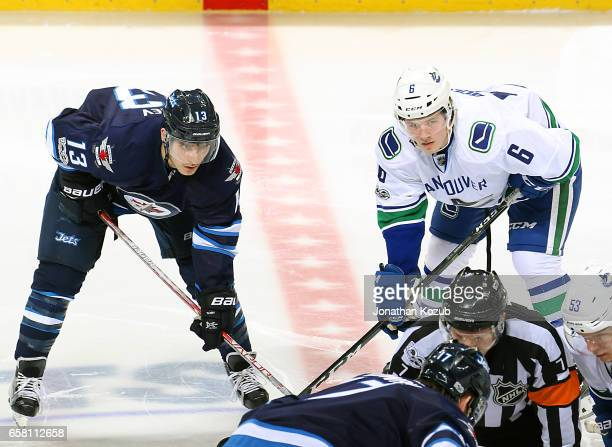 Brandon Tanev of the Winnipeg Jets and Brock Boeser of the Vancouver Canucks line up for a second period faceoff at the MTS Centre on March 26 2017...