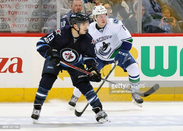 Brandon Tanev of the Winnipeg Jets and Brock Boeser of the Vancouver Canucks keep an eye on the play during third period action at the MTS Centre on...