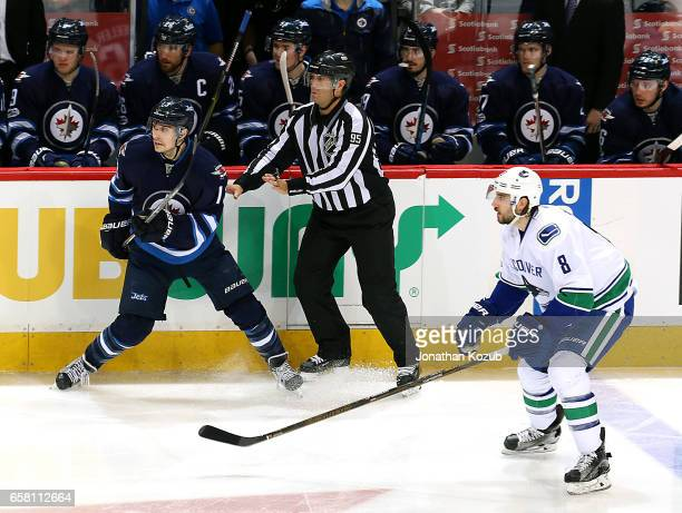 Brandon Tanev of the Winnipeg Jets and Christopher Tanev of the Vancouver Canucks keep an eye on the play during second period action at the MTS...