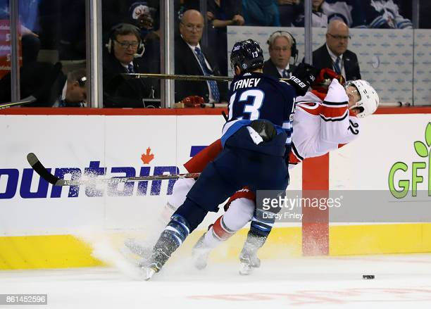 Brandon Tanev of the Winnipeg Jets lays out Brett Pesce of the Carolina Hurricanes with a third period hit at the Bell MTS Place on October 14 2017...