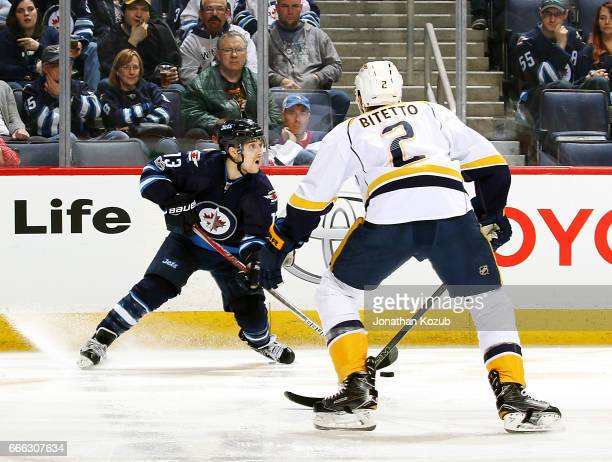 Brandon Tanev of the Winnipeg Jets plays the puck along the boards as Anthony Bitetto of the Nashville Predators defends during second period action...