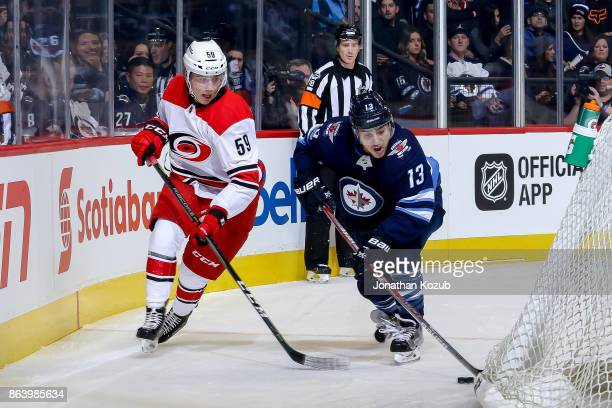 Brandon Tanev of the Winnipeg Jets plays the puck behind the net away from Janne Kuokkanen of the Carolina Hurricanes during first period action at...