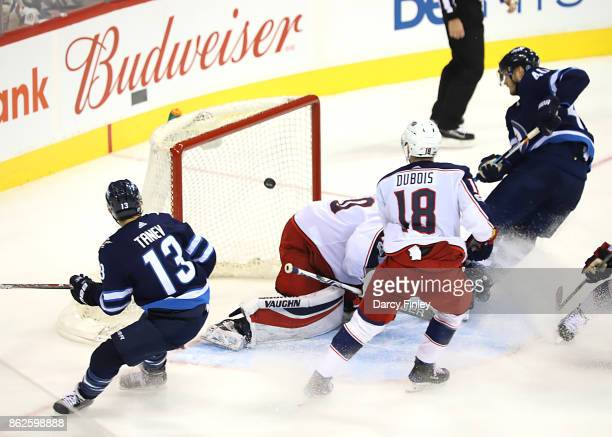 Brandon Tanev of the Winnipeg Jets watches as teammate Joel Armia chips the puck past goaltender Joonas Korpisalo of the Columbus Blue Jackets for a...