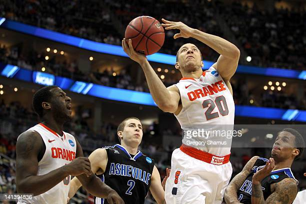 Brandon Triche of the Syracuse Orange makes a layup against Matt Dickey and JP Primm of the UNC Asheville Bulldogs during the second round of the...