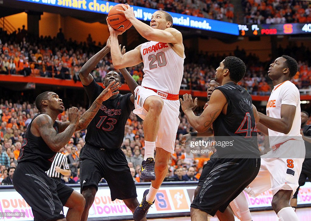 Brandon Triche #20 of the Syracuse Orange puts the ball up to the basket against Jaquon Parker #44, Cheikh Mbodj #13 and Sean Kilpatrick #23 of the Cincinnati Bearcats during the game at the Carrier Dome on January 21, 2013 in Syracuse, New York.