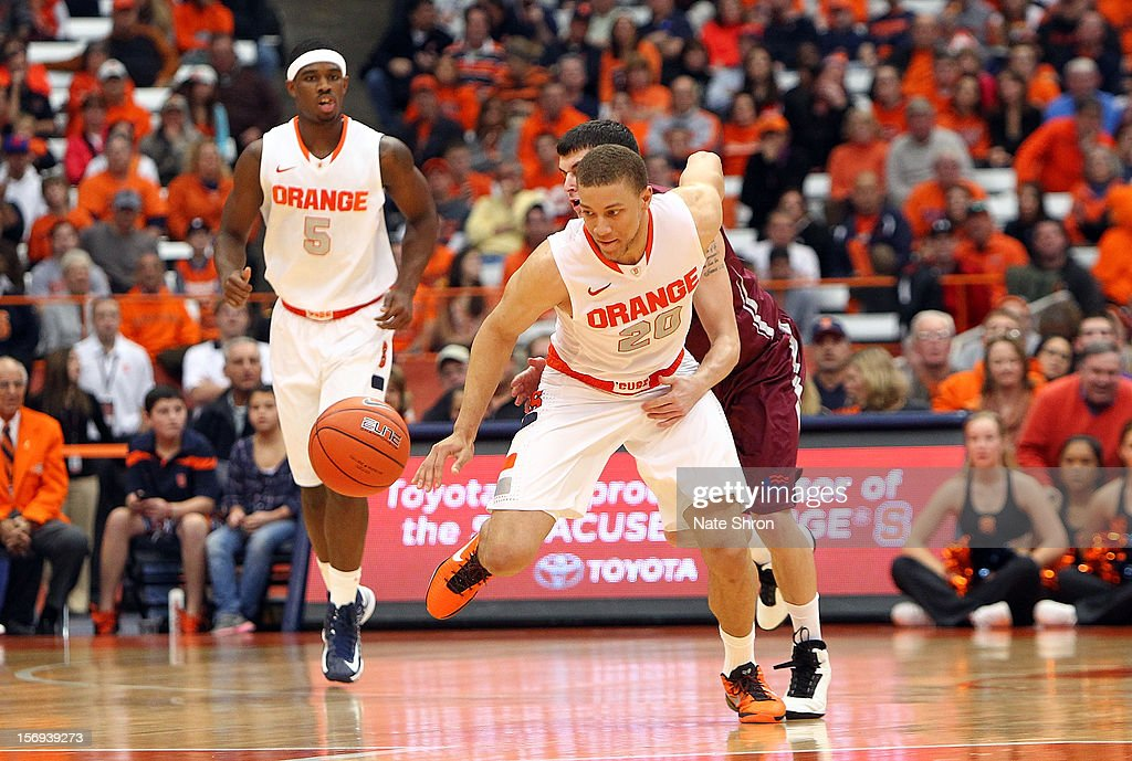 Brandon Triche #20 of the Syracuse Orange reaches for the ball as teammate C.J. Fair looks on against Mitch Rolls #2 of the Colgate Raiders during the game at the Carrier Dome on November 25, 2012 in Syracuse, New York.