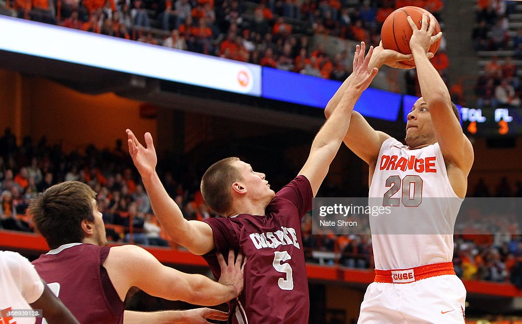 Brandon Triche #20 of the Syracuse Orange shoots the ball against Pat Moore #5 and John Brandenburg #3 of the Colgate Raiders during the game at the Carrier Dome on November 25, 2012 in Syracuse, New York.