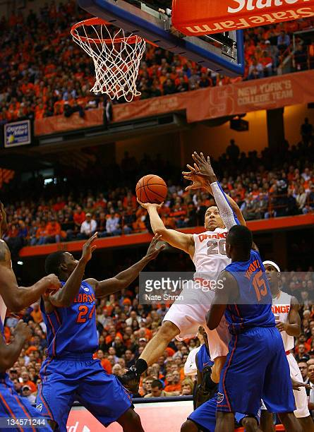 Brandon Triche of the Syracuse Orange shoots the ball against Will Yeguete and Casey Prather of the Florida Gators during the game at the Carrier...