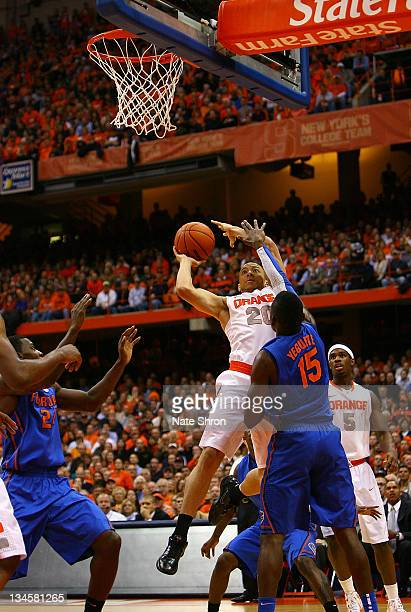 Brandon Triche of the Syracuse Orange shoots the ball against Will Yeguete of the Florida Gators during the game at the Carrier Dome on December 2...