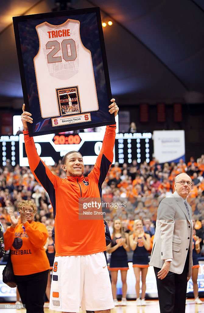 <a gi-track='captionPersonalityLinkClicked' href=/galleries/search?phrase=Brandon+Triche&family=editorial&specificpeople=6516120 ng-click='$event.stopPropagation()'>Brandon Triche</a> #20 of the Syracuse Orange smiles as he holds up his framed jersey during senior night as head coach <a gi-track='captionPersonalityLinkClicked' href=/galleries/search?phrase=Jim+Boeheim&family=editorial&specificpeople=210990 ng-click='$event.stopPropagation()'>Jim Boeheim</a> (R) looks on prior to the game against the DePaul Blue Demons at the Carrier Dome on March 6, 2013 in Syracuse, New York.