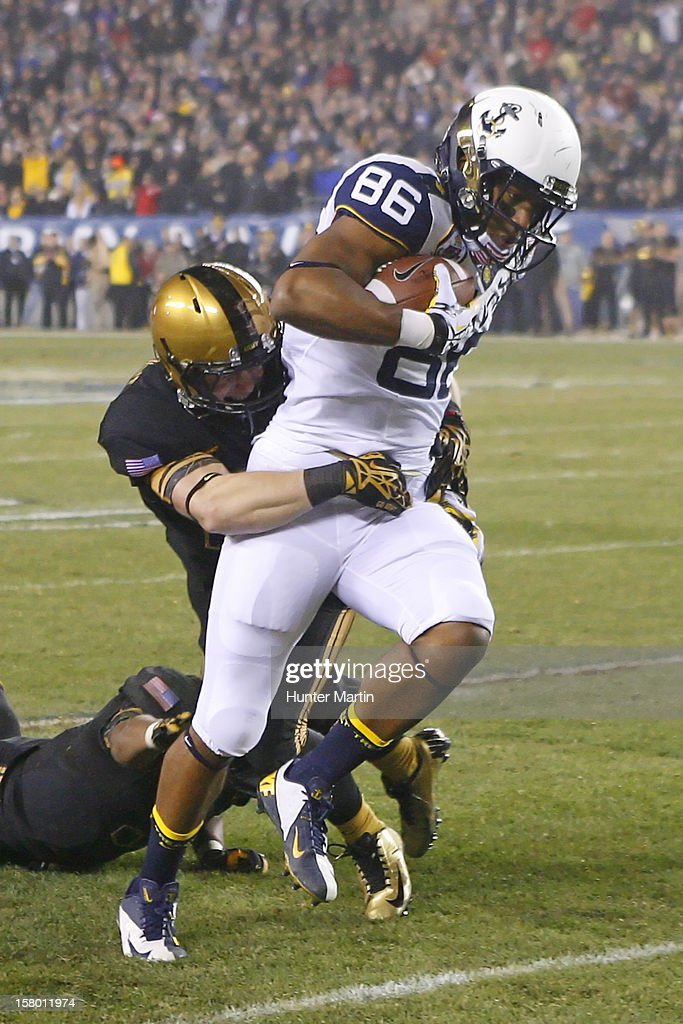 Brandon Turner #86 of the Navy Midshipmen catches a pass as Chris Carnegie #3 of the Army Black Knights makes the tackle during a game on December 8, 2012 at Lincoln Financial Field in Philadelphia, Pennsylvania. The Navy won 17-13.