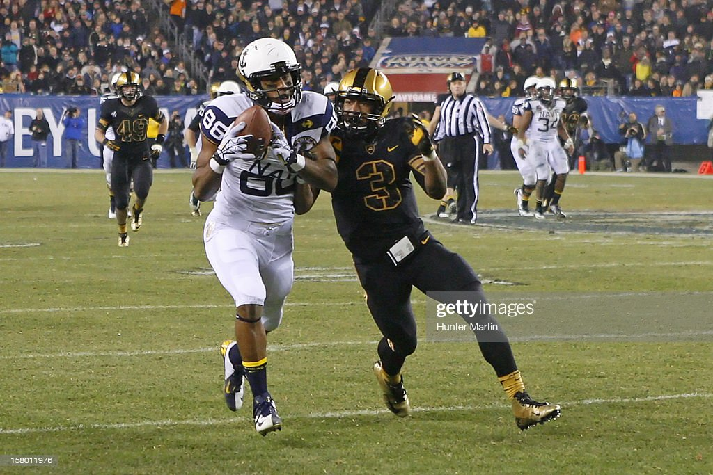 Brandon Turner #86 of the Navy Midshipmen catches a pass as Chris Carnegie #3 of the Army Black Knights defends during a game on December 8, 2012 at Lincoln Financial Field in Philadelphia, Pennsylvania. The Navy won 17-13.