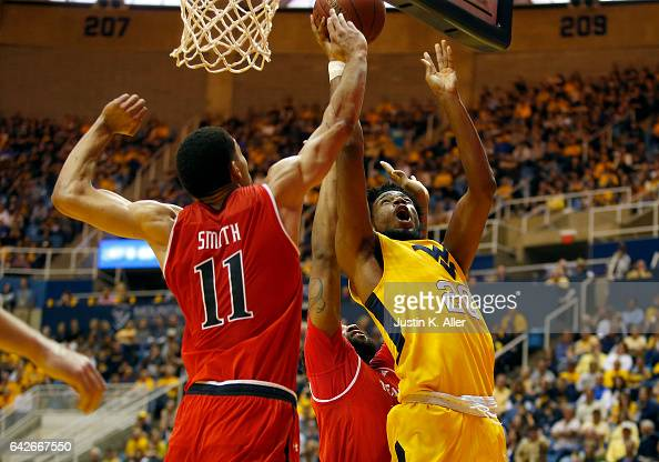 Brandon Watkins of the West Virginia Mountaineers battles under the hoop against Zach Smith of the Texas Tech Red Raiders at the WVU Coliseum on...