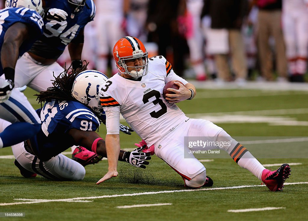 Brandon Weeden of the Cleveland Browns slides for a first down past Ricardo Mathews of the Indianapolis Colts at Lucas Oil Stadium on October 21 2012...