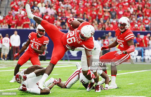 Brandon Wilson of the Houston Cougars gets tripped up on a return in the first half of their game against the Oklahoma Sooners during the Advocare...