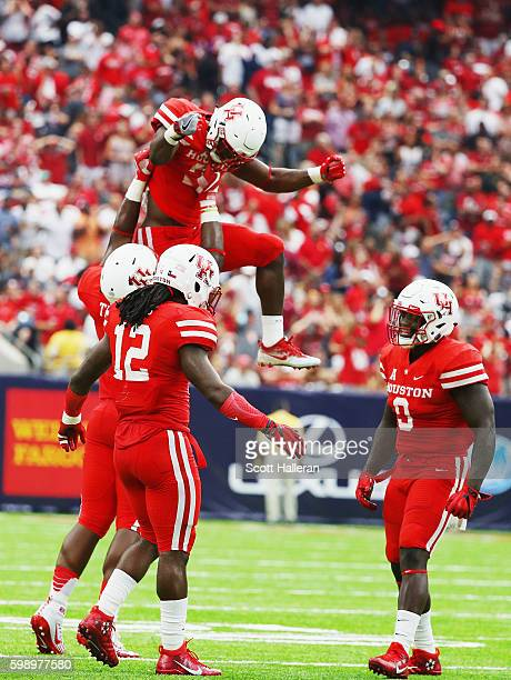 Brandon Wilson of the Houston Cougars leaps into the air near his teammates during the second half of their game against the Oklahoma Sooners during...