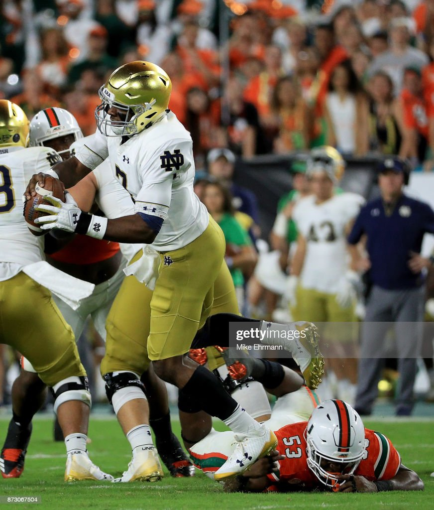 Brandon Wimbush #7 of the Notre Dame Fighting Irish is tripped up by Zach McCloud #53 of the Miami Hurricanes during a game at Hard Rock Stadium on November 11, 2017 in Miami Gardens, Florida.