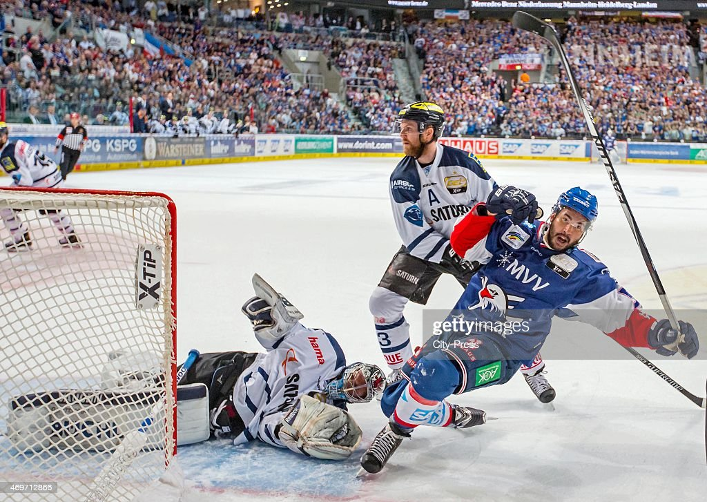 Brandon Yip of the Adler Mannheim Derek Hahn of ERC Ingolstadt and Timo Pielmeier of ERC Ingolstadt fight for the puck during the game between Adler...