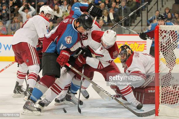 Brandon Yip of the Colorado Avalanche tries to collect the puck in the crease as Eric Belanger of the Phoenix Coyotes defends and goalie Jason...