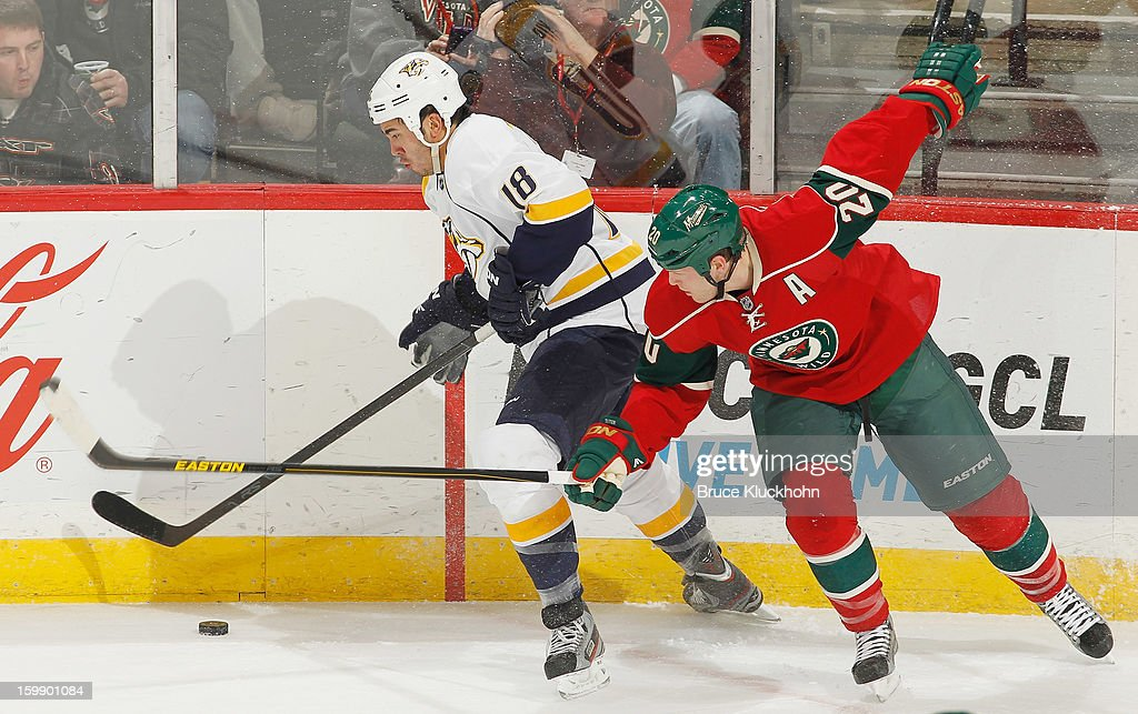 Brandon Yip #18 of the Nashville Predators handles the puck along the boards with Ryan Suter #20 of the Minnesota Wild defending during the game on January 22, 2013 at the Xcel Energy Center in Saint Paul, Minnesota.