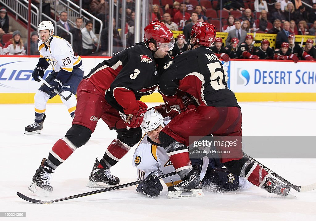 Brandon Yip #18 of the Nashville Predators is checked by Keith Yandle #3 and Derek Morris #53 of the Phoenix Coyotes during the NHL game at Jobing.com Arena on January 28, 2013 in Glendale, Arizona. The Coyotes defeated the Predators 4-0.