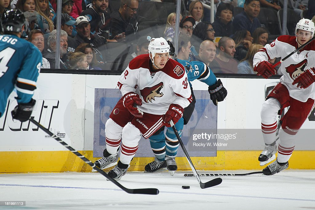 Brandon Yip of the Phoenix Coyotes skates with the puck against Bracken Kearns of the San Jose Sharks during a preseason NHL game at SAP Center on...
