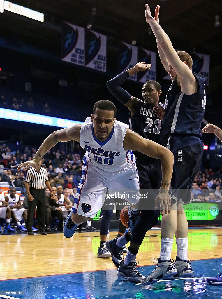 Brandon Young #20 of the DePaul Blue Demons hits the floor after losing the ball under pressure from Aaron Bowen #23 and Nate Lubick #34 of the Georgetown Hoyas at the Allstate Arena on February 3, 2014 in Rosemont, Illinois. Georgetown defeated DePaul 71-59.