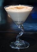 A creamy white cocktail called the Brandy Alexander. Topped with a sprinkle of nutmeg.