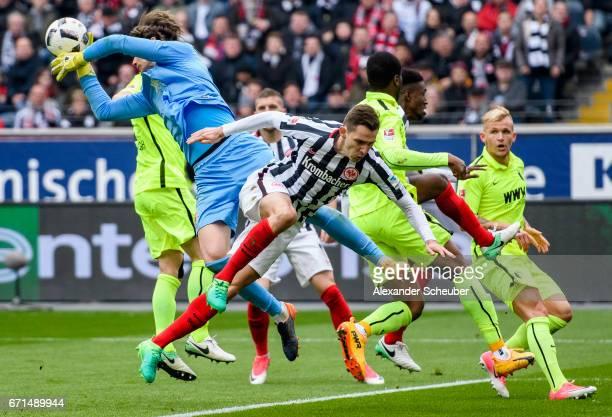 Branimir Hrgota of Frankfurt challenges Marwin Hitz of Augsburg during the Bundesliga match between Eintracht Frankfurt and FC Augsburg at...