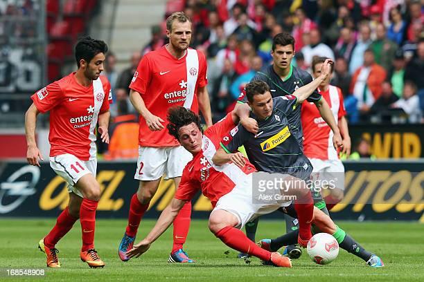 Branimir Hrgota of Moenchengladbach is challenged by Julian Baumgartlinger Bo Svensson and Yunus Malli of Mainz during the Bundesliga match between 1...