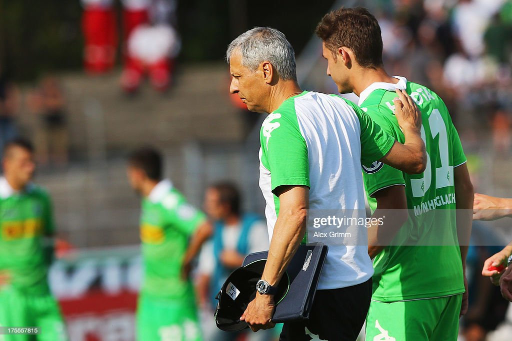 Branimir Hrgota of Moenchengladbach is comforted by head coach Lucien Favre after he missed the final penalty during the penalty shoot-out of the DFB Cup first round match between Darmstadt 98 and Borussia Moenchengladbach at Boellenfalltorstadion on August 4, 2013 in Darmstadt, Germany.