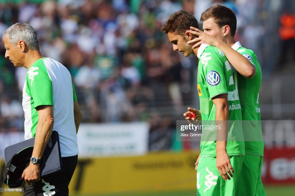 Branimir Hrgota of Moenchengladbach is comforted by team mate Havard Nordtveit after he missed the final penalty during the penalty shoot-out of the DFB Cup first round match between Darmstadt 98 and Borussia Moenchengladbach at Boellenfalltorstadion on August 4, 2013 in Darmstadt, Germany.