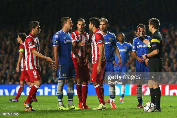 Branislav Ivanovic and John Terry of Chelsea confront Diego Costa of Club Atletico de Madrid after he delayed his penalty kick during the UEFA...