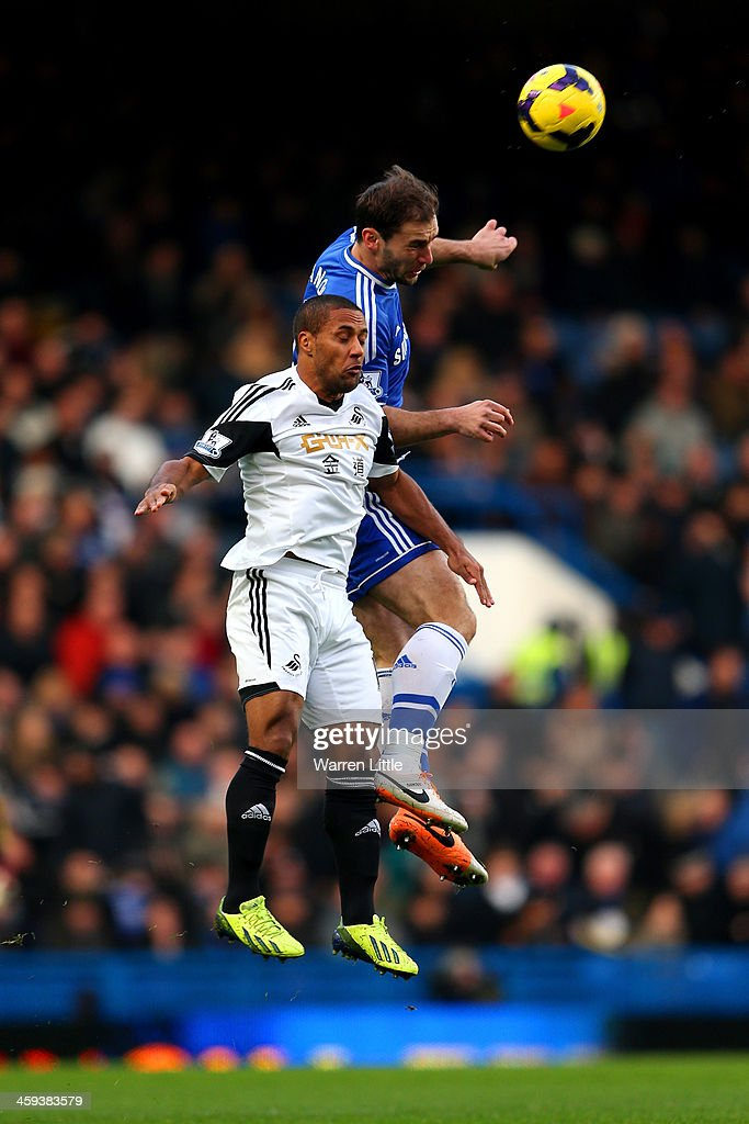 Branislav Ivanovic of Chelsea beats Wayne Routledge of Swansea City to the ball during the Barclays Premier League match between Chelsea and Swansea City at Stamford Bridge on December 26, 2013 in London, England.