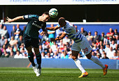 Branislav Ivanovic of Chelsea heads the ball clear of Karl Henry of QPR during the Barclays Premier League match between Queens Park Rangers and...