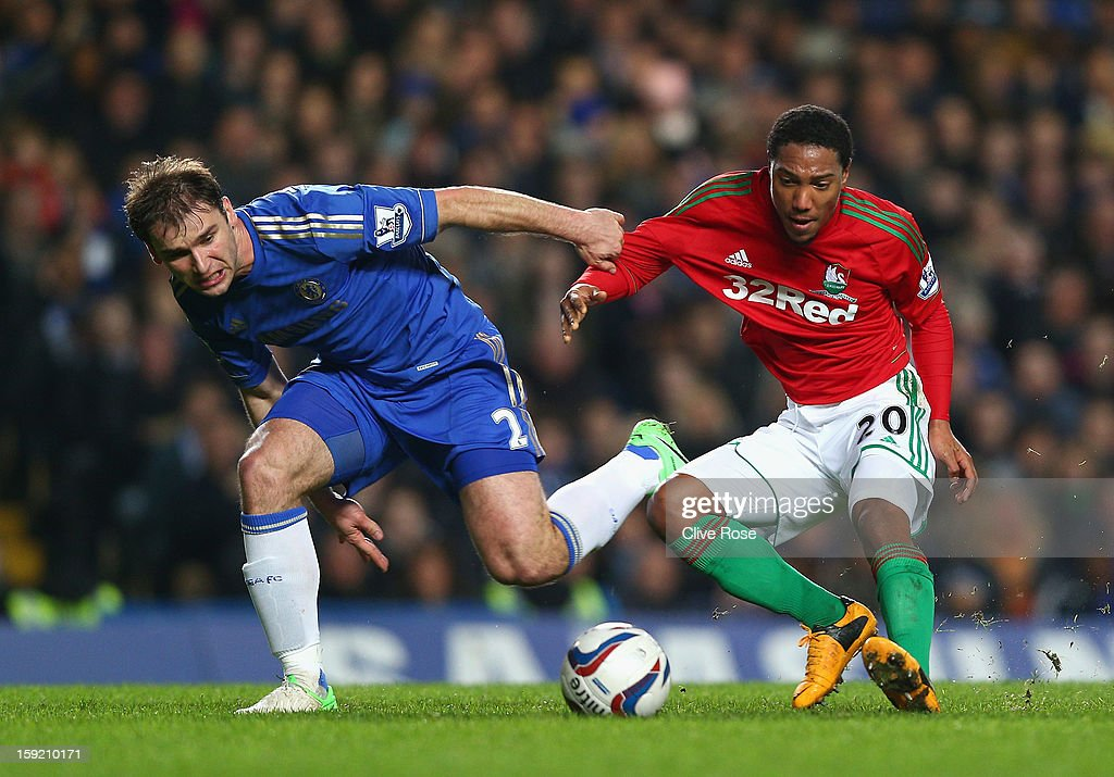 Branislav Ivanovic of Chelsea is challenged by Jonathan de Guzman of Swansea City during the Capital One Cup Semi-Final first leg match between Chelsea and Swansea City at Stamford Bridge on January 9, 2013 in London, England.