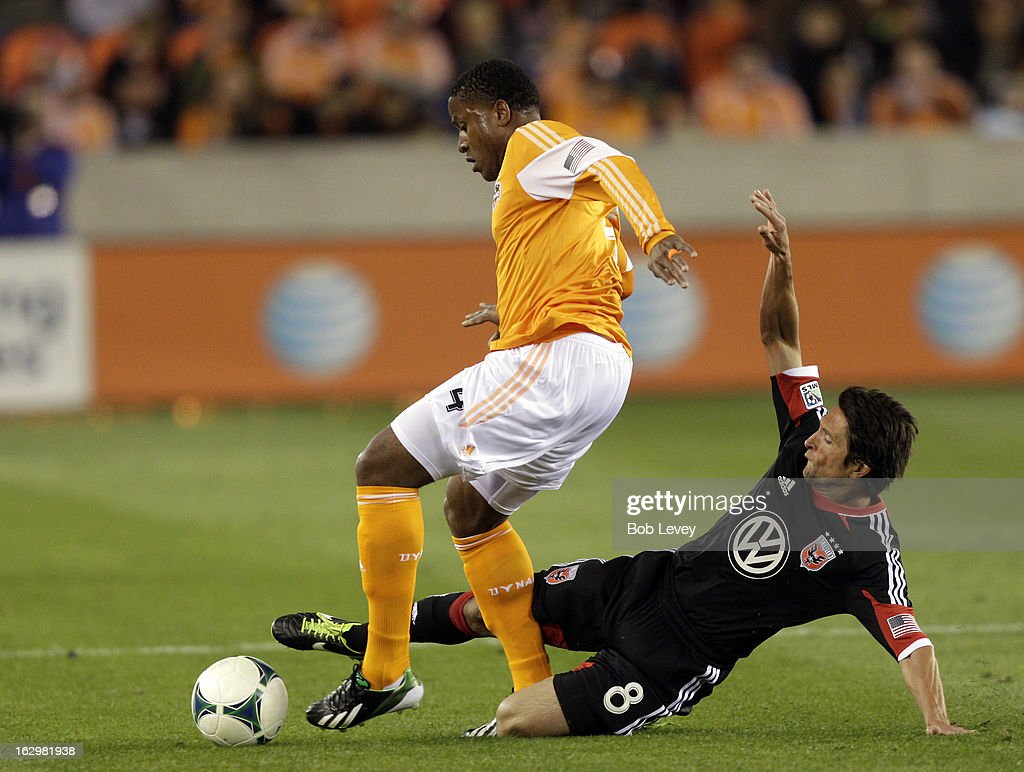 Branko Boskovic #8 of the D.C. United makes a sliding tackle on Jermaine Taylor #4 of the Houston Dynamo during first half action at BBVA Compass Stadium on March 2, 2013 in Houston, Texas.