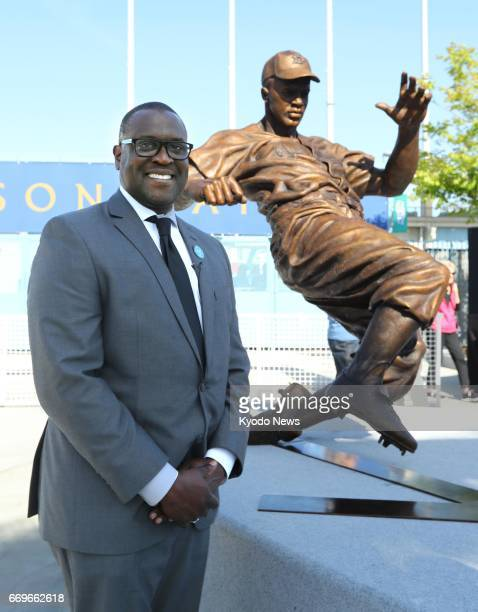 Branly Cadet sculptor of the new Jackie Robinson bronze statue poses alongside his work at Dodger Stadium in Los Angeles on April 15 the 70th...