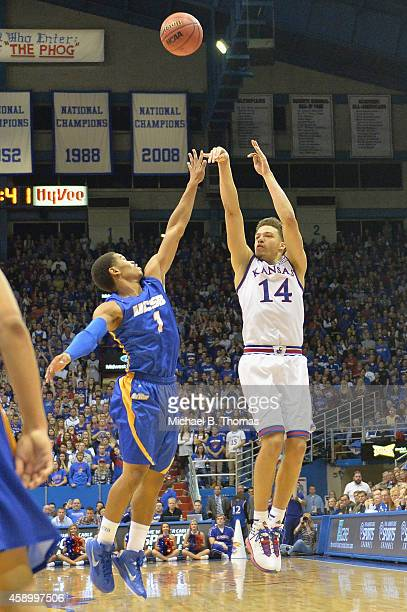 Brannen Greene of the the Kansas Jayhawks shoots over Eric Childress of the UC Santa Barbara Gauchos in the first half at Allen Fieldhouse on...