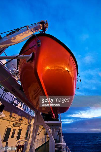 A bright orange emergency rescue lifeboat on a ship in Antarctica.