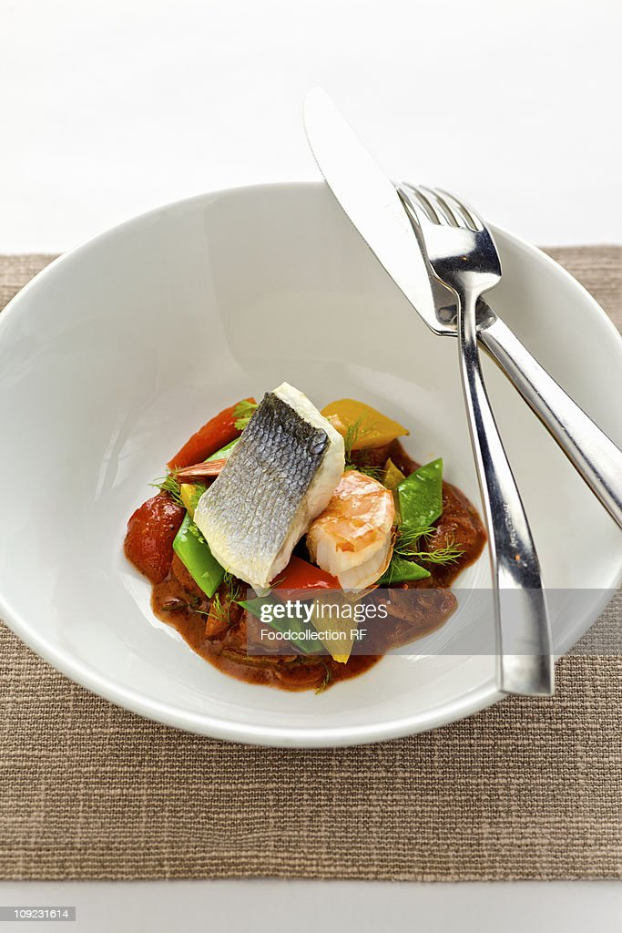Branzino and prawns with vegetables in bowl, close-up : Stock Photo