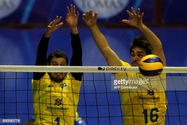 Brasilian Bruno Rezende and Lucas Saatkamp try to block the smash of Venezuelan Ronald Fayola during their Men's South American Volleyball...