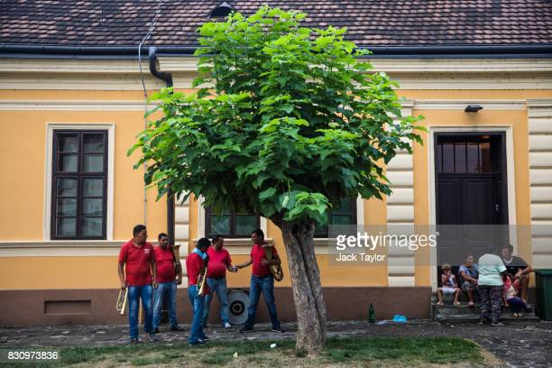 A brass band gathers by a tree in the town centre during the Guca Trumpet Festival on August 11 2017 in Guca Serbia Thousands of revellers attend the...