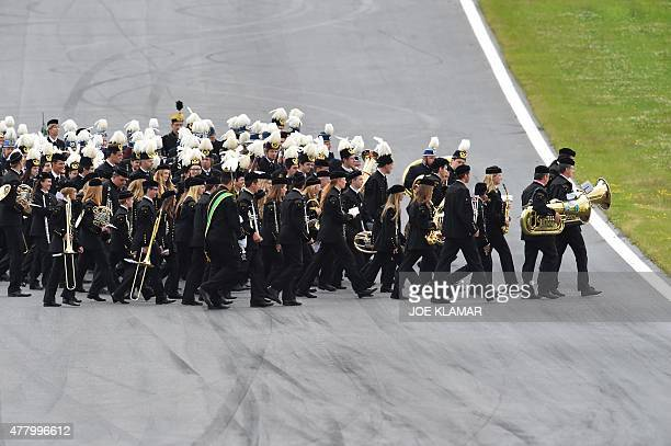 A brass band leaves the course ahead of the start of the Austrian Formula One Grand Prix on the Red Bull Ring racing circuit in Spielberg Austria on...