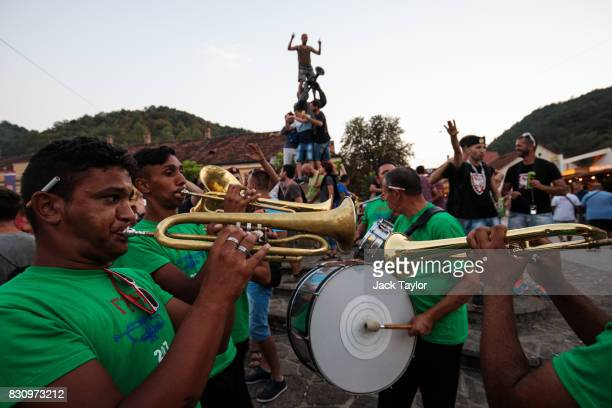 A brass band performs in the town centre in front of the Guca trumpeter statue during the Guca Trumpet Festival on August 11 2017 in Guca Serbia...