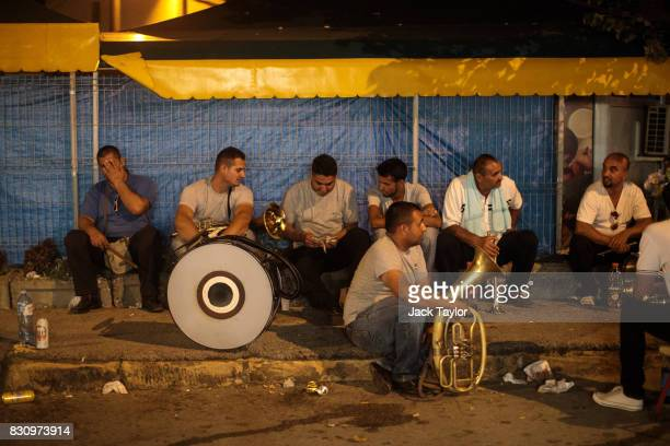 A brass band relax on the street in town during the Guca Trumpet Festival on August 12 2017 in Guca Serbia Thousands of revellers attend the trumpet...