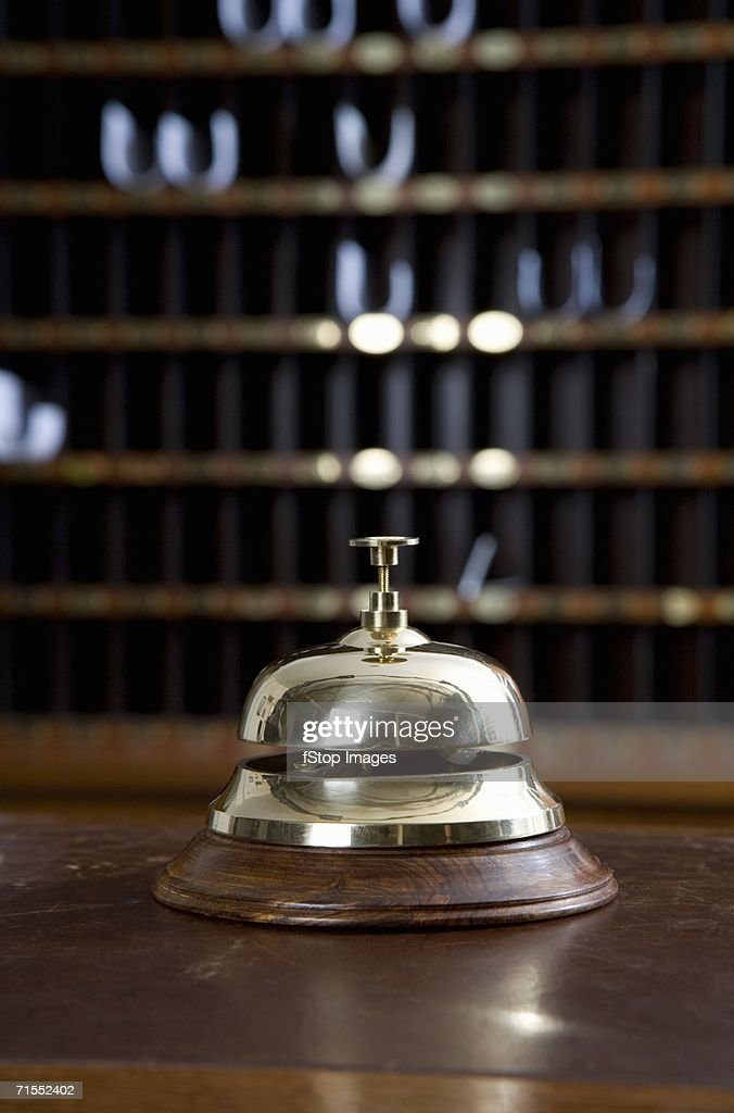 Brass bell on desk at hotel reception : Stock Photo