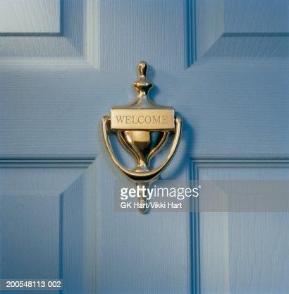 Brass door knocker on front door engraved with word 'welcome', close-up