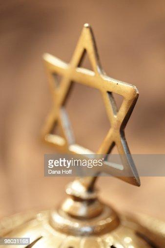 brass Jewish cross on brown background